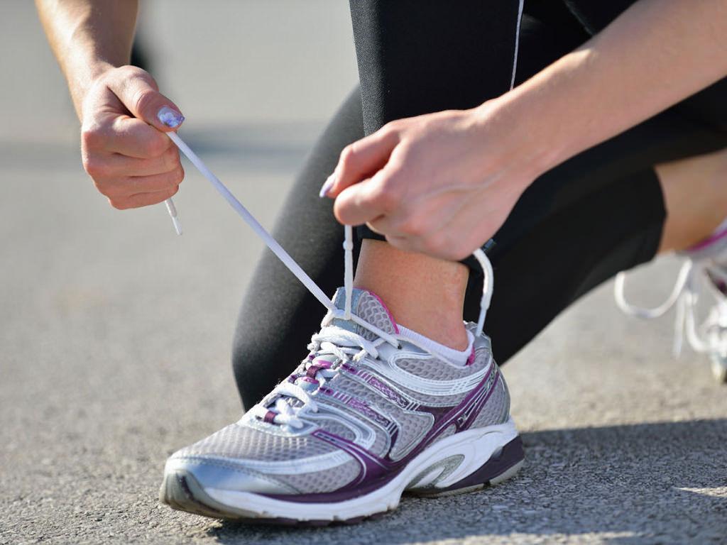 Donna che si allaccia la scarpa da tennis